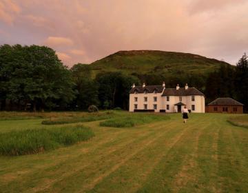 Abendliches Knock House mit Regenbogen und einem Schotten